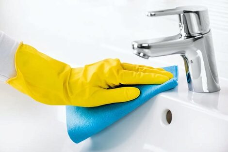 Yellow gloved hand disinfecting sink