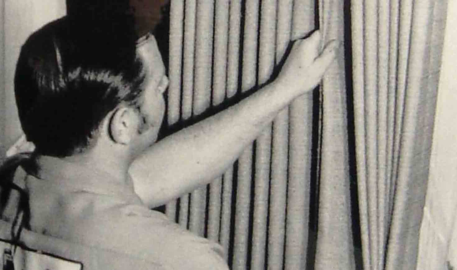 black and white photo of technician adjusting drapes